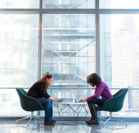 dos mujeres reunidas en oficinas de one-click