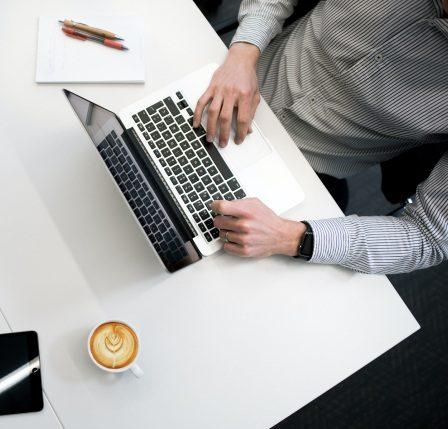 Vista desde arriba de hombre trabajando con su laptop